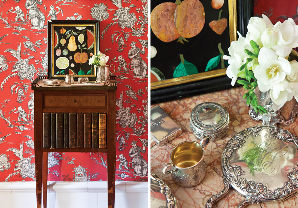 Red chinoiserie wallpaper brightens the powder room, where an English table with fretted gallery trim displays antique silver pieces.