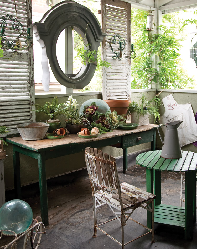 An antique zinc oval window frame from an old French château, a pair of distressed wooden shutters, and a primitive garden table.