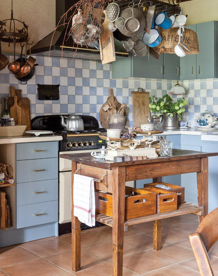 "The kitchen features blue and white tiles found in a French market and a wooden table once used for drying cheeses. ""Our interior decoration is not something we managed in a short period,"" says Clementine, ""but is the result of a lifetime of collecting nice brocante furniture and vintage items."" Come see 36 Best Beautiful Blue and White Kitchens to Love! #blueandwhite #bluekitchen #kitchendesign #kitchendecor #decorinspiration #beautifulkitchen"